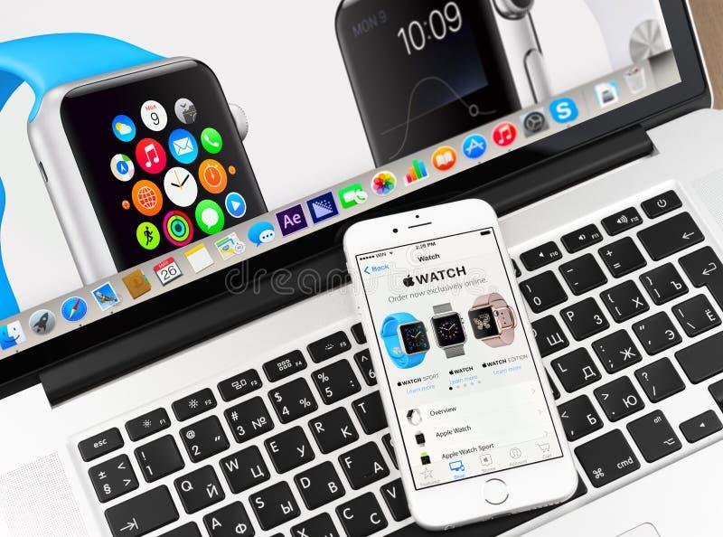 Apple-horloge op iPhone 6 en Macbook-vertoning stock foto's