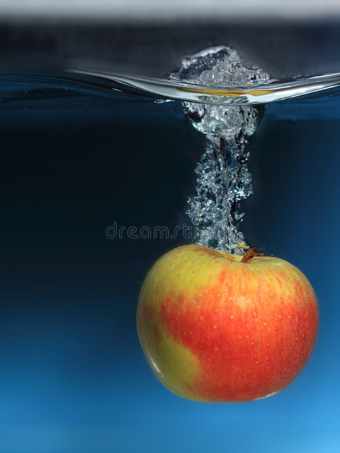 Apple im Wasser spritzen über blauem Hintergrund lizenzfreies stockfoto