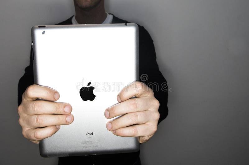 Apple ipad 2. NEW YORK - MARCH 26: happy casual boy holds is newly released apple ipad 2 on 26th of march, 2011, in new york ,USA.Tablet market is growing year royalty free stock images