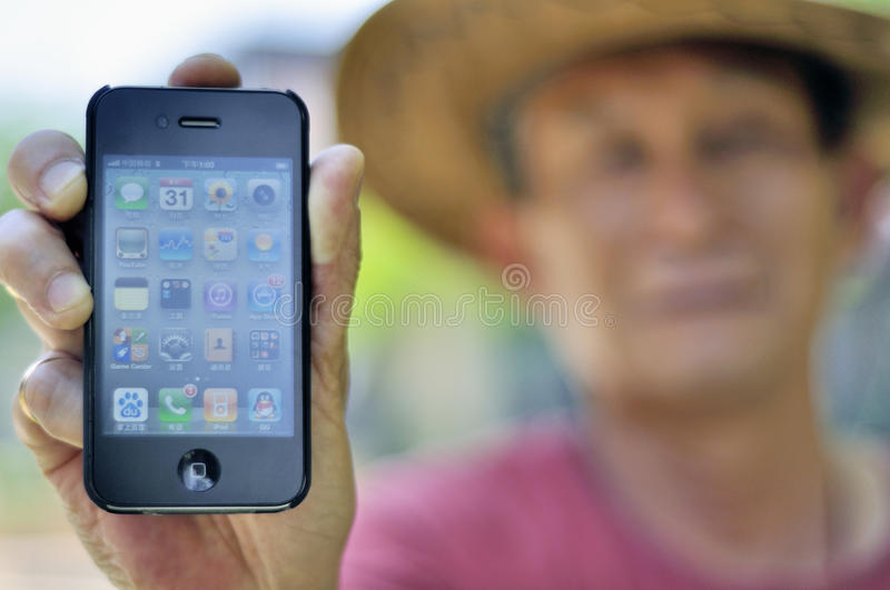 Apple iPhone 4. Chinese man holding the phone stock photography