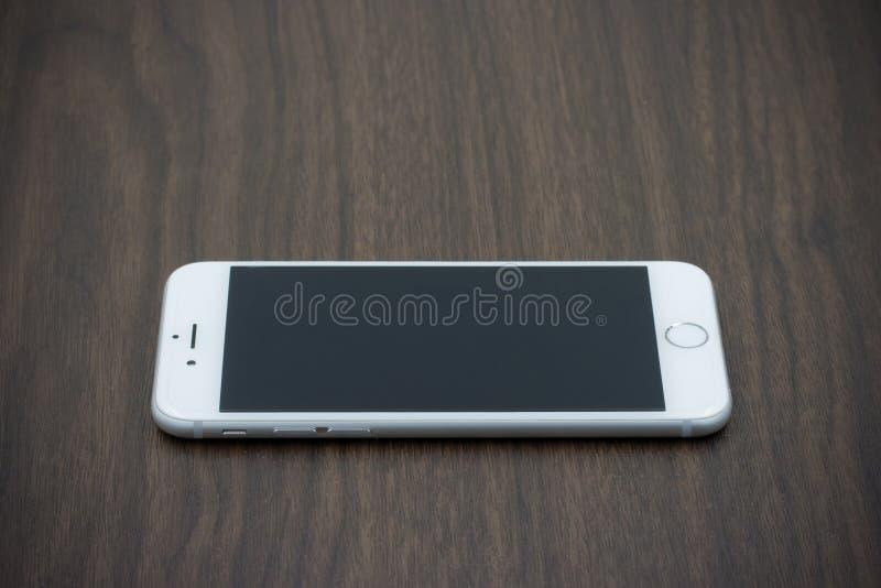 Apple Iphone 6 i vit färg med den tomma skärmen som lägger på trä royaltyfri foto
