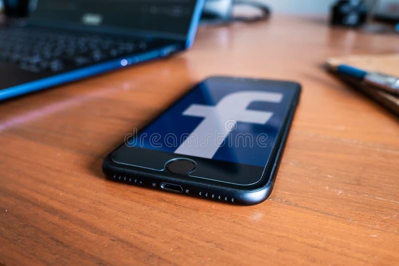 Apple iPhone 7 op een bureau die het zijn scherm met Facebook-embleem tonen stock foto