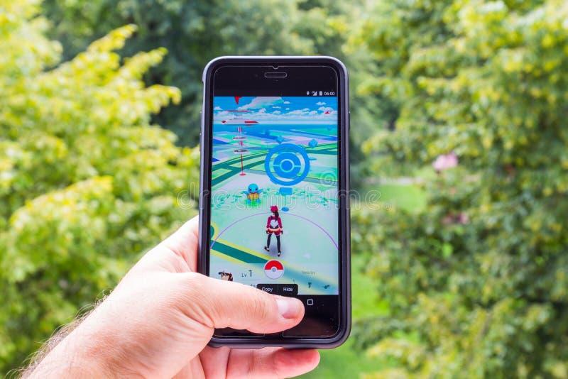 Apple iPhone6 più tenuto in una mano che mostra il suo schermo con Pokemon va l'applicazione fotografie stock libere da diritti