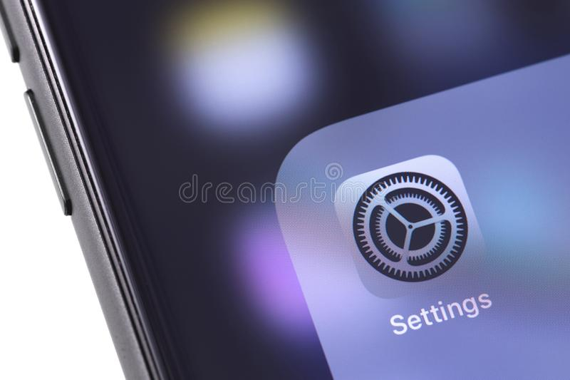 Apple iPhone with Settings app icon on the screen. Apple Inc. is stock photos