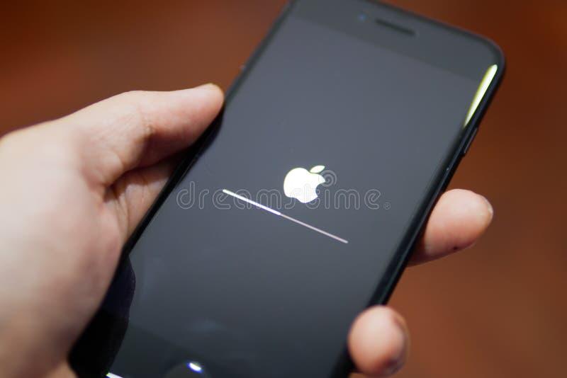 Apple iPhone 7 som visar dess skärm med den Apple logoen, när det uppdateras programvaran till iOS 12 royaltyfria foton