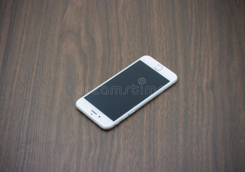 Apple Iphone 6 in white color with blank screen laying on wooden. BANGKOK, THAILAND - MAY 7, 2015. Apple Iphone 6 in white color with blank screen laying on stock images