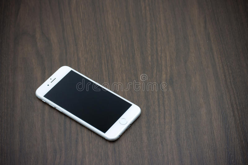 Apple iPhone 6 in white color with blank screen laying on wooden. BANGKOK, THAILAND - MAY 7, 2015. Apple iPhone 6 in white color with blank screen laying on stock photos