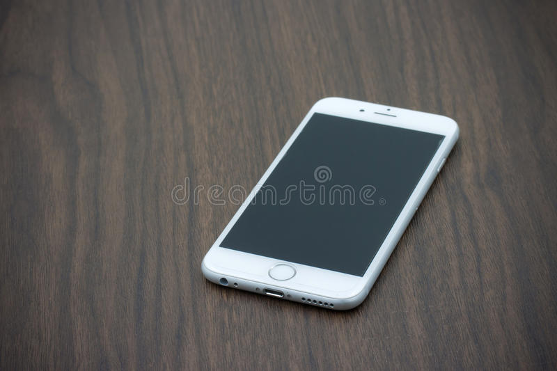 Apple Iphone 6 in white color with blank screen laying on wooden. BANGKOK, THAILAND - MAY 7, 2015. Apple Iphone 6 in white color with blank screen laying on royalty free stock photo
