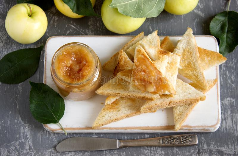 Apple jam in a glass jar with bread toasts and ripe apples on a wooden surface. Rustic style. royalty free stock photos