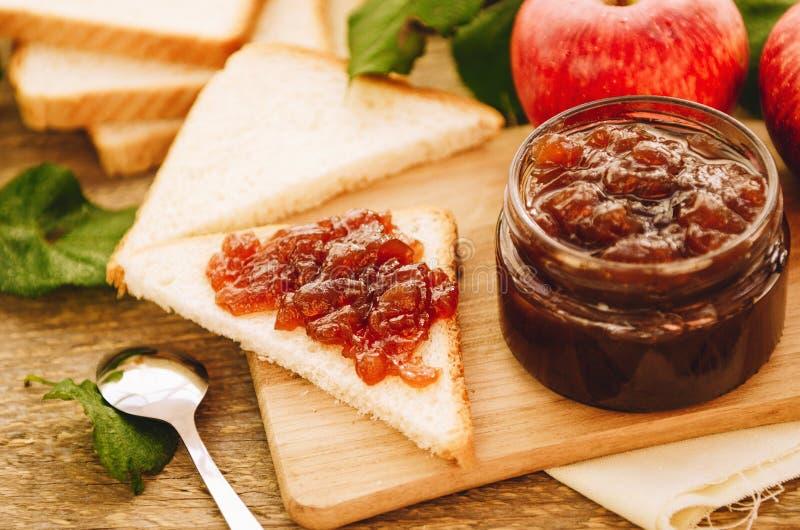 Apple-jam op toost en in kruik, verse rode appelen op een scherpe raad op een houten lijst Heerlijk ontbijt, rustieke stijl royalty-vrije stock afbeeldingen