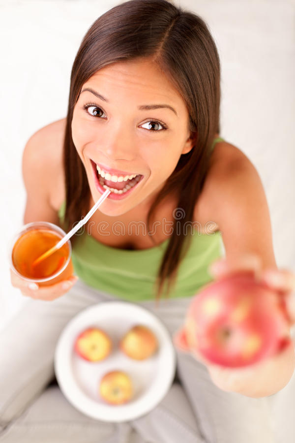 Apple juice. Woman drinking  showing apples. Happy excited and cheerful young female model royalty free stock photo