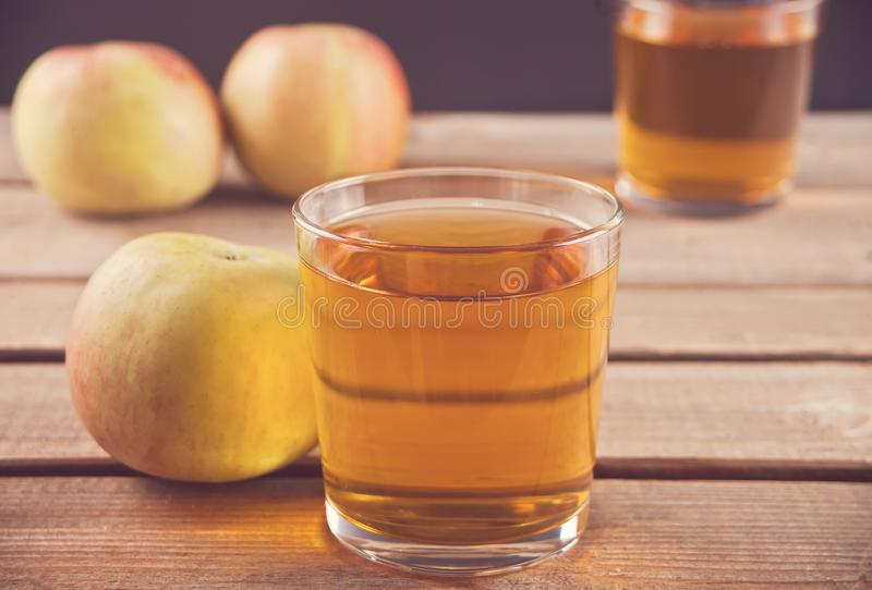 Apple juice and apples on wooden table. Selective focus stock photos