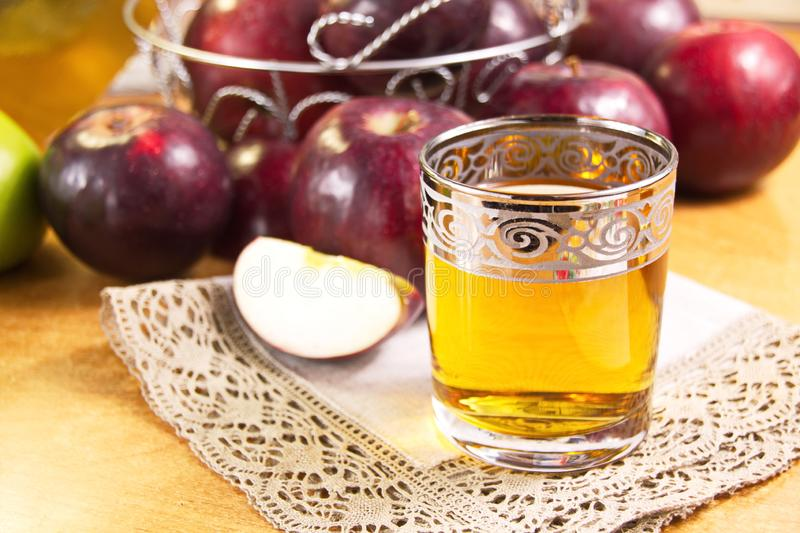 Apple juice clarified in a glass and fresh red apples. Are a delicious healthy drink royalty free stock image