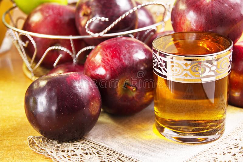 Apple juice clarified in a glass and fresh red apples. Are a delicious healthy drink stock photos