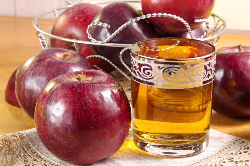 Apple juice in a glass Cup and red apples on the table royalty free stock images