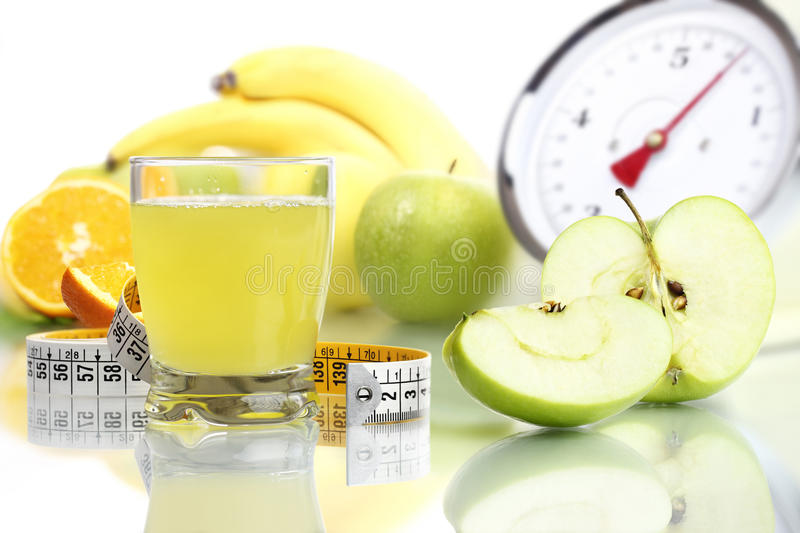 Apple juice in glass, fruit meter scales diet food. Concept royalty free stock photography