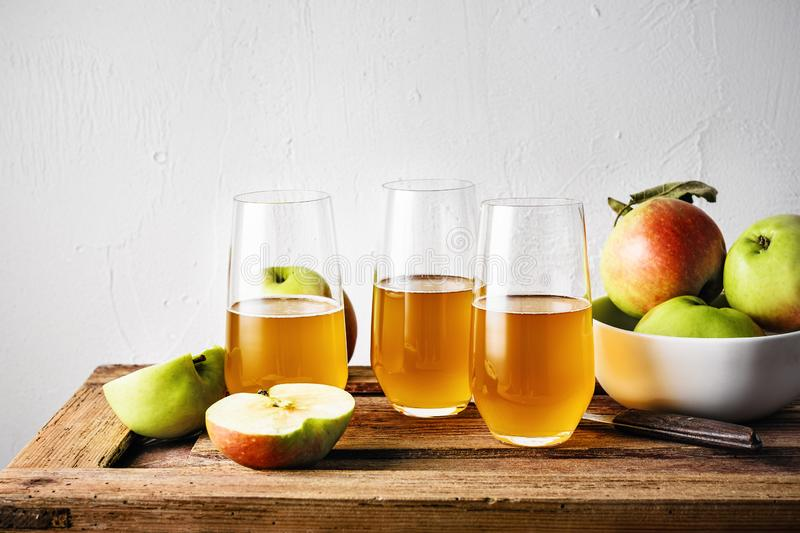 Apple juice. Glasses of fresh apple juice and apples on a wooden table stock images