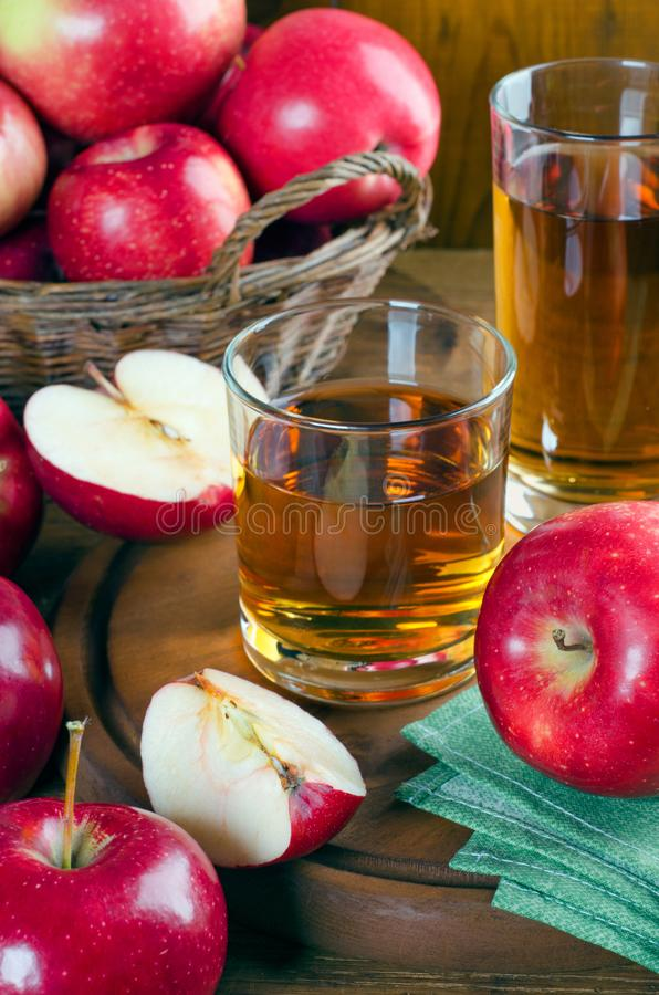 Apple juice in glasses and ripe red apples stock photos