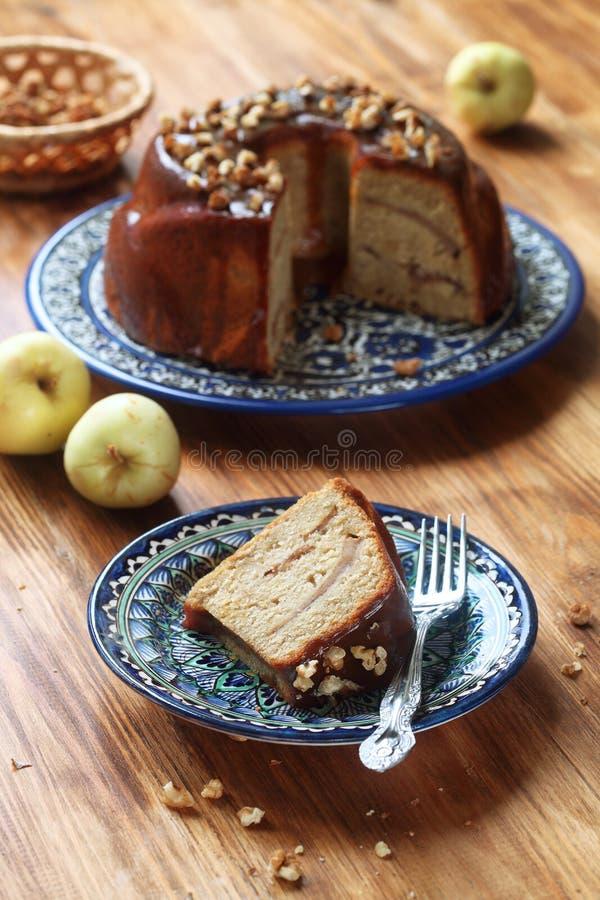 Apple kaka med karamelltoppningskivan och valnötter arkivbilder