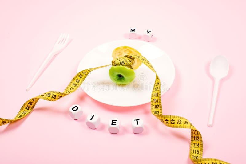 Apple-kern met het meten van band in plaats van de taille op een witte plaat met tekst MIJN DIEET op roze achtergrond Het dieet,  royalty-vrije stock afbeelding