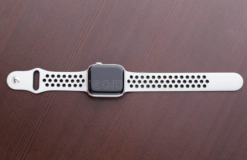 Apple klocka Nike + Försilvra aluminiumfallet med ren platina på träbakgrund arkivfoto