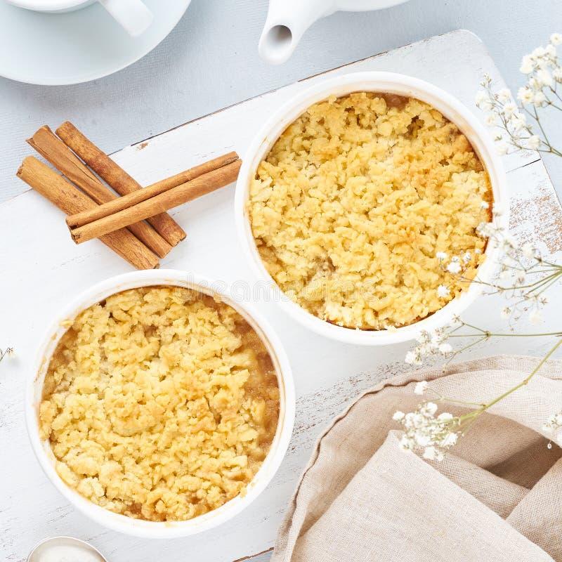 Apple-Krümel mit Streusel auf hellgrauer Tabelle Morgenfrühstück mit Blumen stockbilder