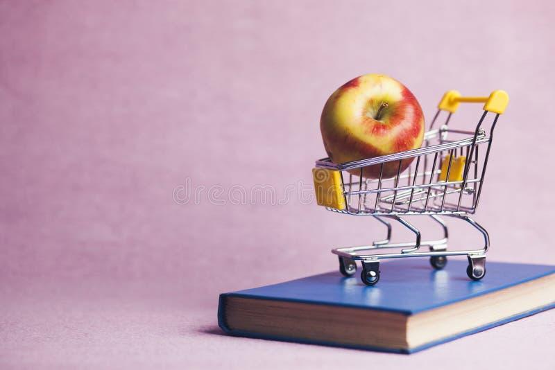 Apple, książka i wózek na zakupy, zdjęcia stock