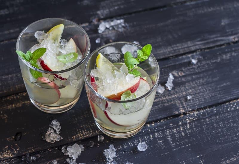 Apple, lemon and mint homemade lemonade. On a dark wooden background stock photos