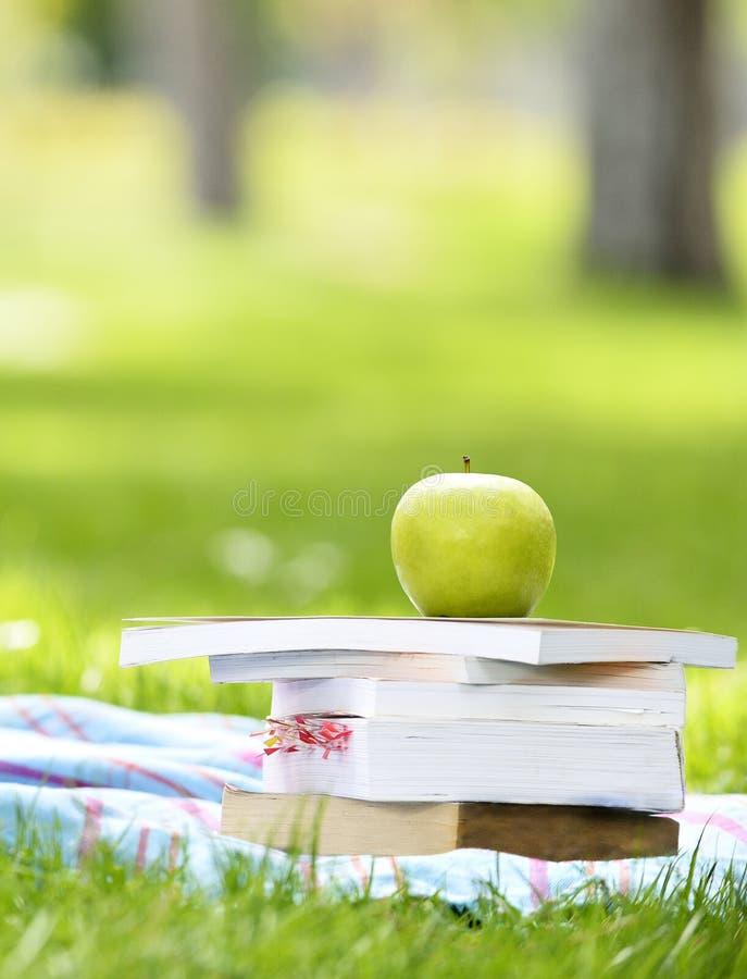 Apple, libri di concetto del libro e cuffie immagine stock
