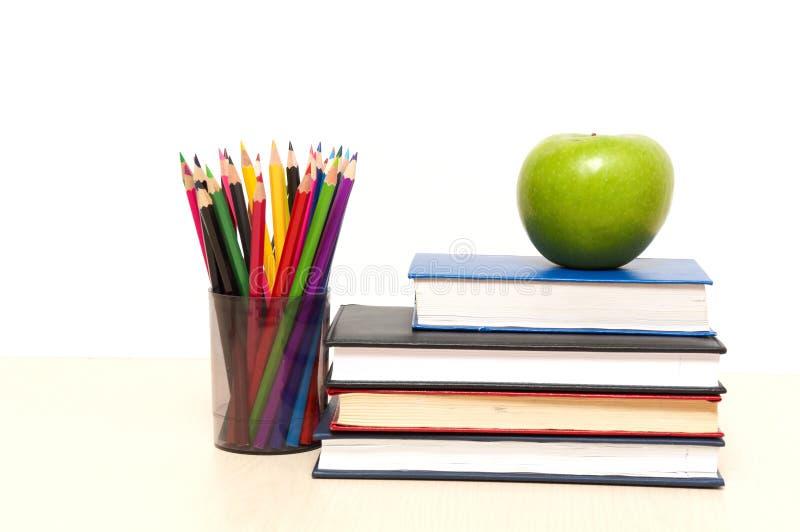 Apple, libros y lápiz coloreado imagen de archivo