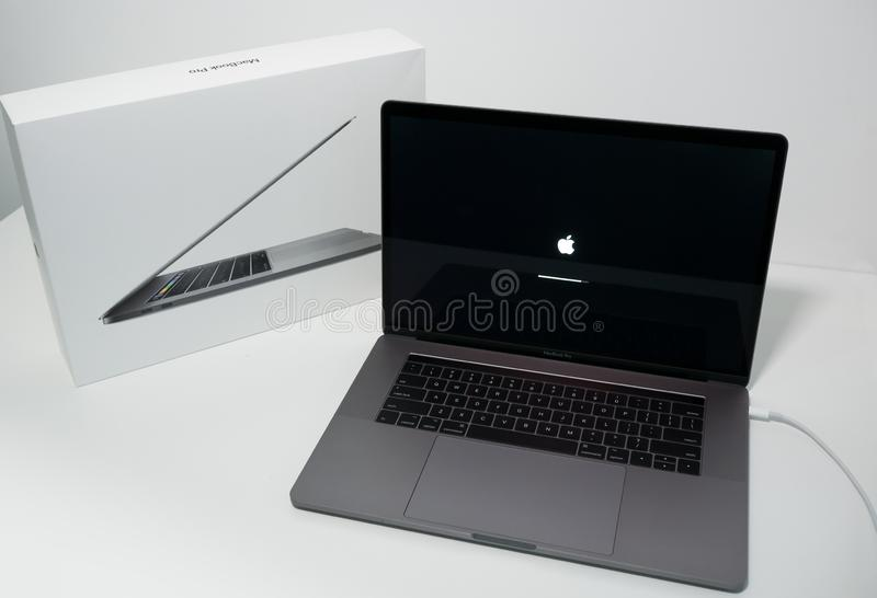 Apple MacBook Pro 15 inch notebook computer with touchbar. Apple MacBook Pro 15 inch notebook computer with touch bar. On a white desk with box stock images