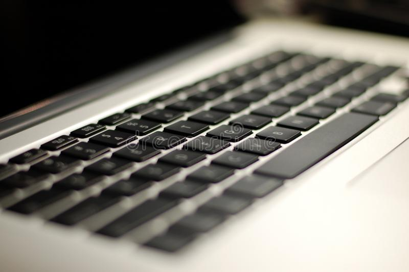 2015 Apple Macbook Pro Laptop Keyboard Closeup. Close up of 2015 Apple Macbook Pro laptop keyboard with blur royalty free stock photos