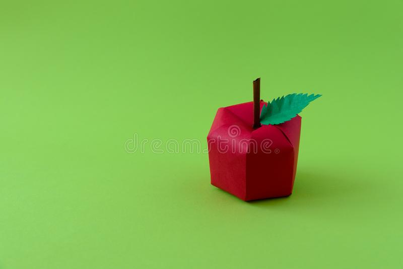 Apple made from paper on green background. Fresh fruits. Minimal, creative, vegan, healthy or food art concept. Copy space.  royalty free stock image
