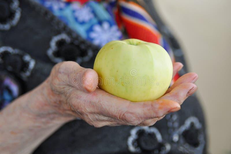 Apple maduro na mão de uma mulher idosa em uma veste feita malha para uma caminhada 90 anos Saúde e nutrição Close-up foto de stock royalty free