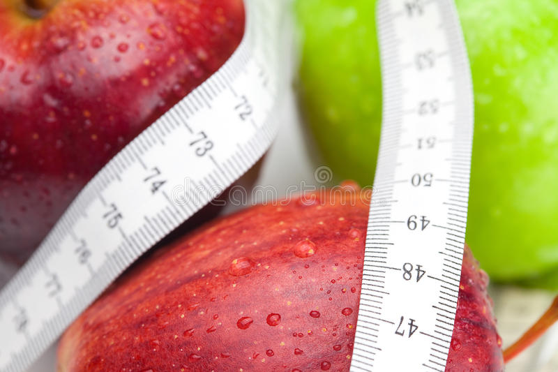 Apple and measure tape. Apple with water drops and measure tape royalty free stock images