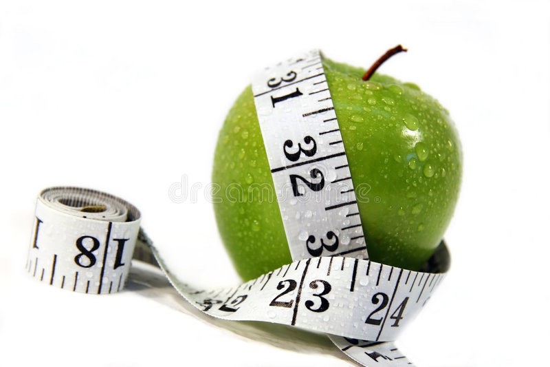 Apple and measurement tape. Measurement tape wrapped around green apple/Concept for health, diet royalty free stock photography