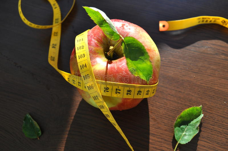 Apple and measurement tape stock photography
