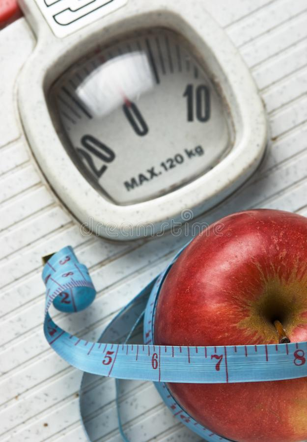 Apple and measuring tape on the floor scales. Isolated on white royalty free stock photo