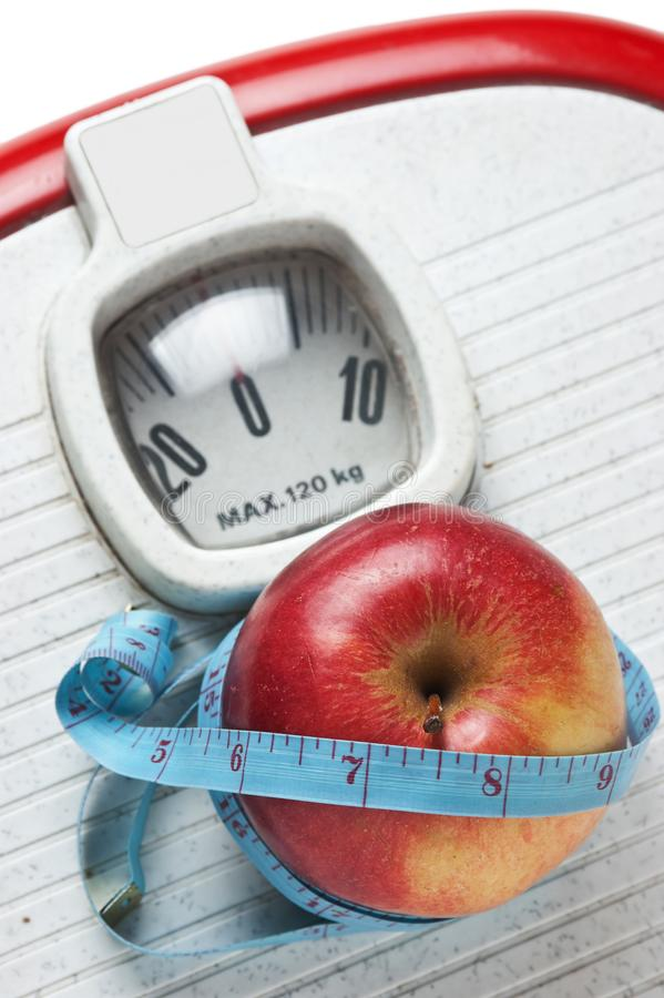 Apple and measuring tape on the floor scales. On white stock photography