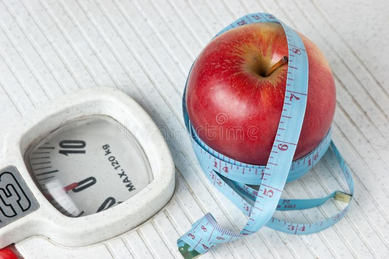 Apple and measuring tape on the floor scales. Isolated on white stock images