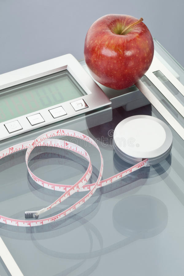 Apple and measuring tape on scales. On grey background royalty free stock image