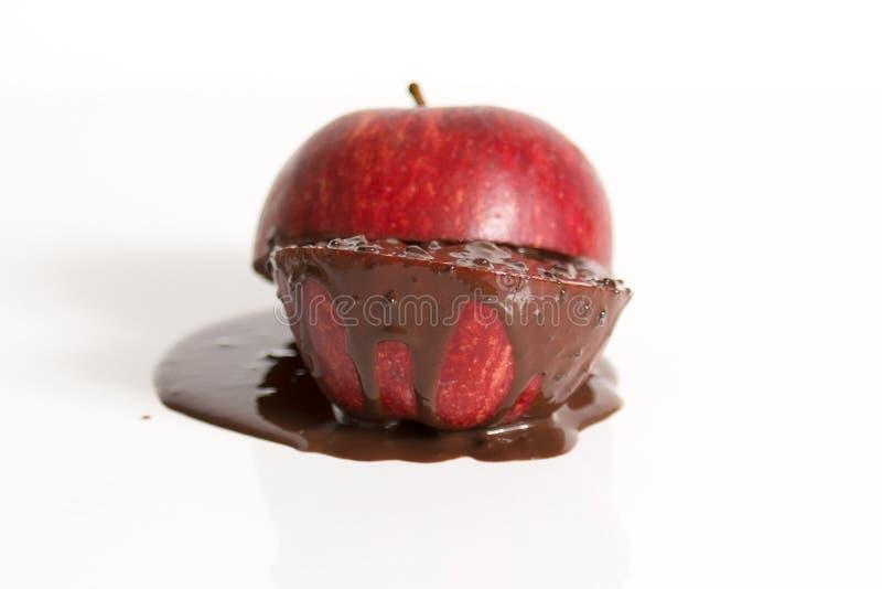 Apple met donkere chocolade die uit afscheiden stock fotografie