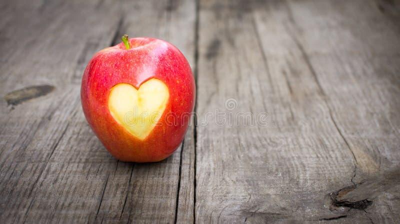 Apple met gegraveerd hart stock afbeeldingen
