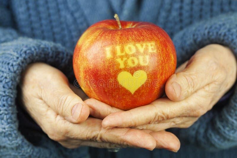 Apple met inschrijving I liefde u op oude vrouwen` s handen stock afbeelding