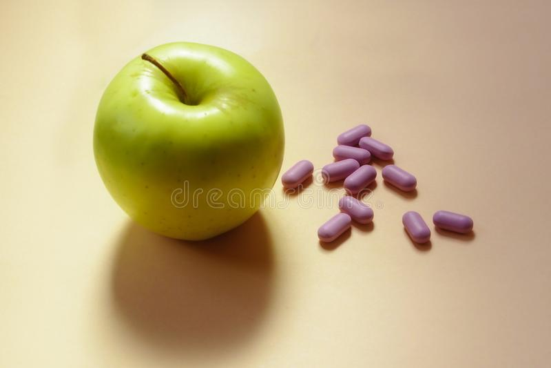 Apple met kleurenpillen stock foto