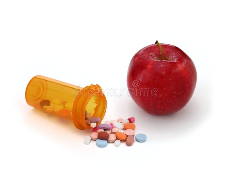 Apple mit verschütteten Pillen vom Dram stockbild