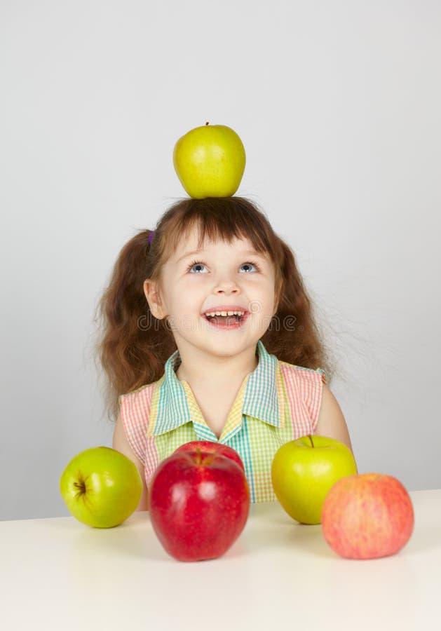 Apple na cabeça de uma menina alegre foto de stock
