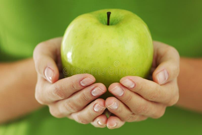 Apple nas mãos da mulher foto de stock royalty free