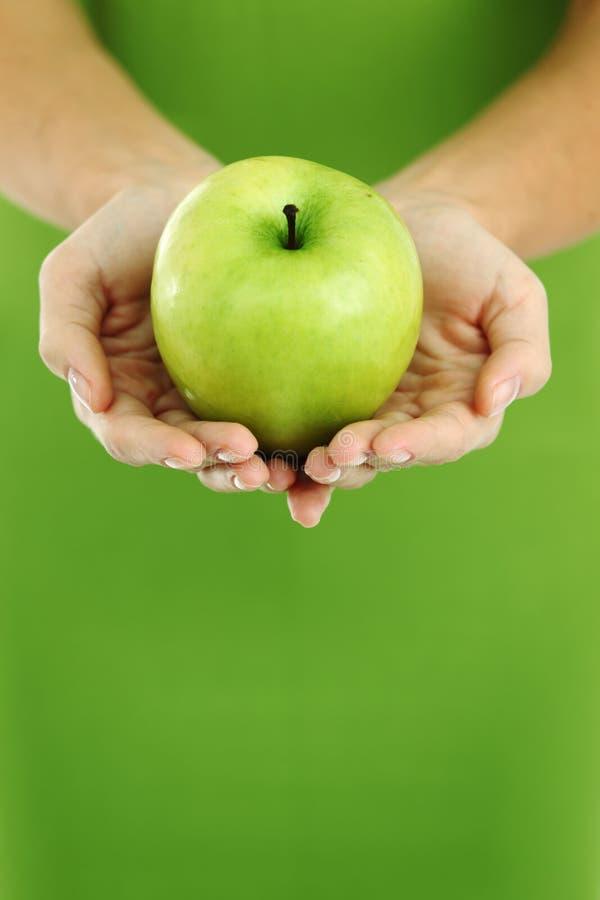 Apple nas mãos da mulher foto de stock