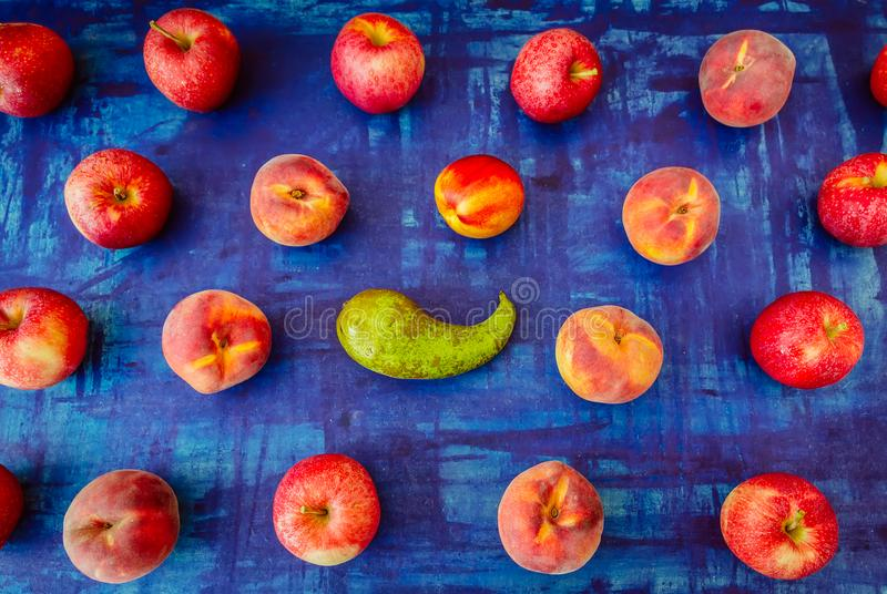 Apple with nectarine, peach and pear in rows on blue background, raw healhy food concept royalty free stock images